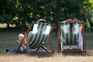 Heatwave alert in Britain, a couple relax on deckchairs in Hyde Park