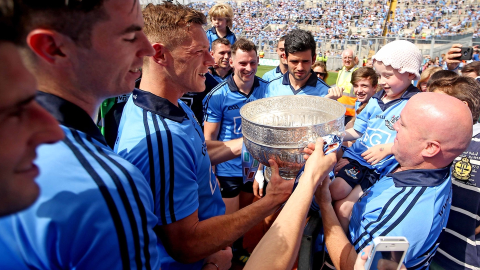Dublin players bring the trophy to fan Molly McNally