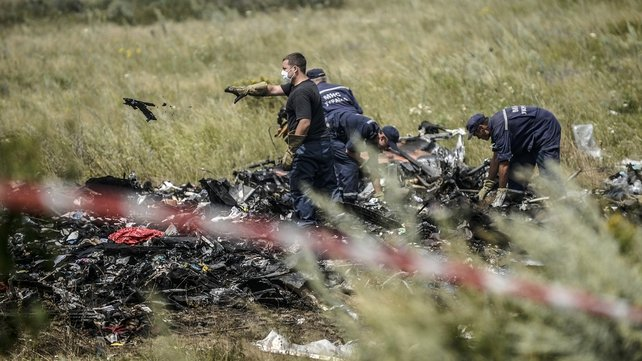 Ukrainian State Emergency Service employees collect bodies of victims at the crash site