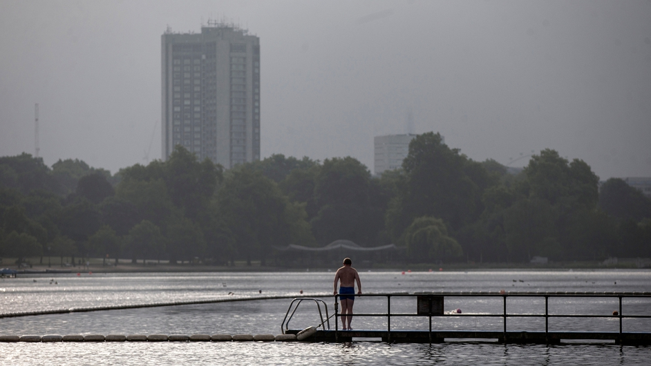 A swimmer takes an early morning dip in Serpentine lake in Hyde Park, London