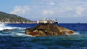 The rock which the Costa Concordia cruise ship, which is being refloated in the background, struck