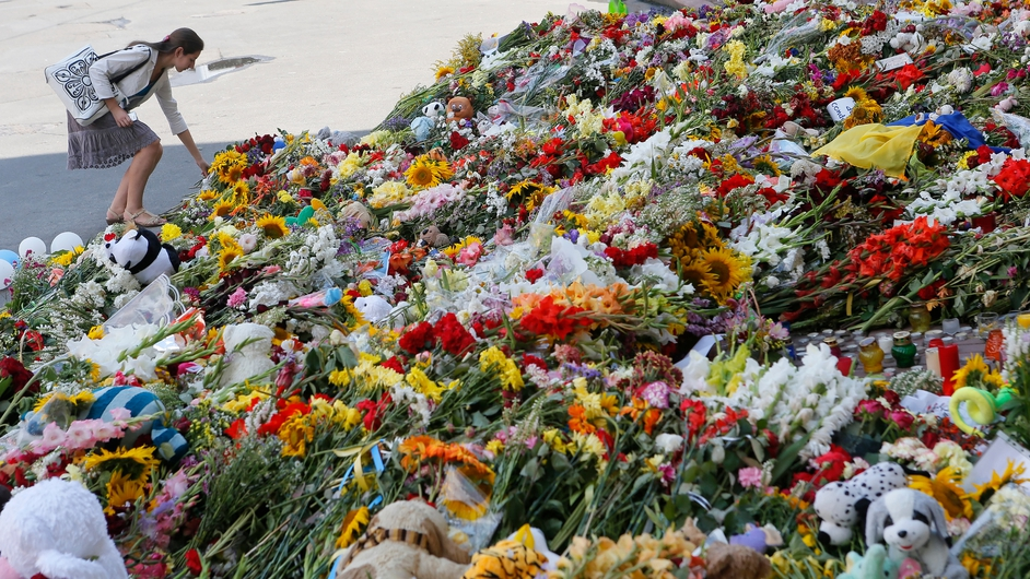 A woman lays flowers at a tribute to the victims of MH17 at the Dutch embassy in Kiev