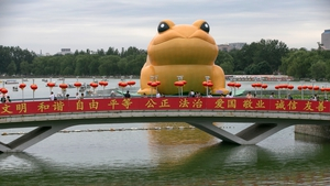A giant inflatable 'Golden Toad' is displayed on a lake as visitors cross a bridge in Beijing, China