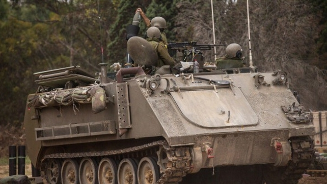 Israeli soldiers fire mortars from an armored personnel carrier near the Israeli-Gaza border