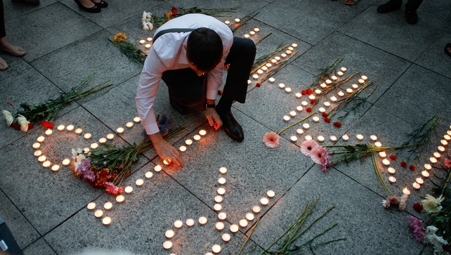 A man lights candles during a vigil for the victims in Kuala Lumpur, Malaysia