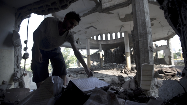 A Palestinian man inspects the rubble of a destroyed mosque