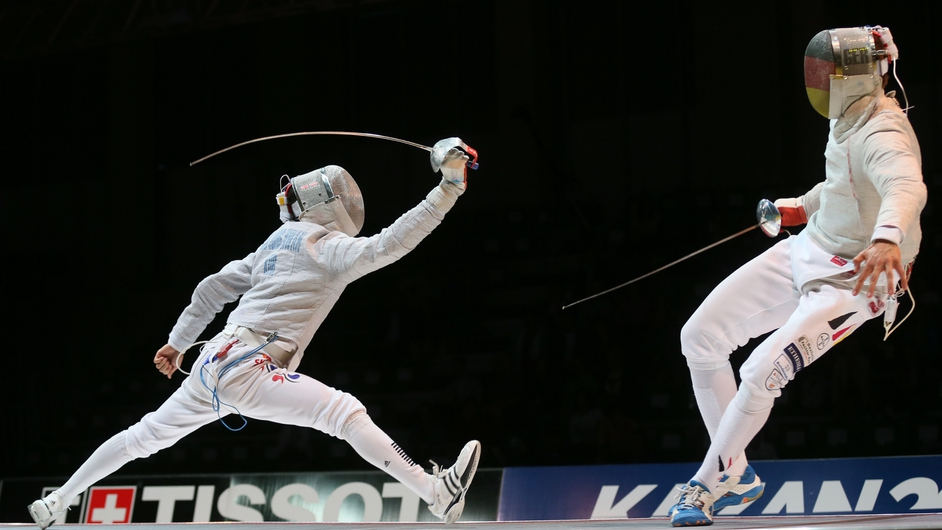 Junghwan Kim (L) of Korea fights with Benedikt Wagner of Germany during their Men's team Sabre match at the FEI 2014 Fencing World Championships in Kazan, Russia