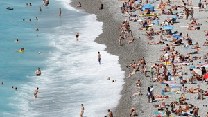 People enjoy the sun and sea on a crowded beach in Nice, southern France