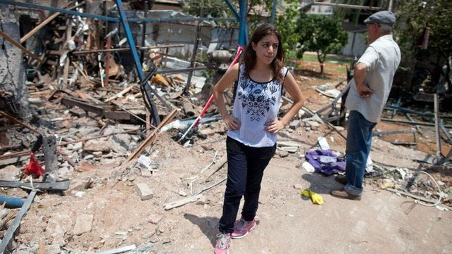 An Israeli woman inspects an Israeli home hit by a Hamas rocket in Yahud south ofTel Aviv