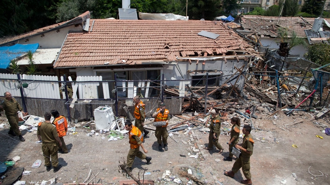 Israeli troops inspect a house hit by Hamas rockets in Yahud