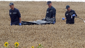Ukrainian personnel remove a body from the crash site