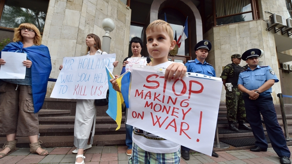 A young boy holds a sign during a demonstration in front of the French Embassy in Kiev