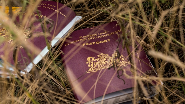 Two Dutch passports lie in a field among luggage, personal belongings and wreckage from the plane