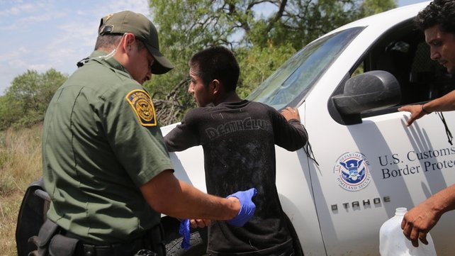 Border Patrol agents search an undocumented immigrant after taking him into custody