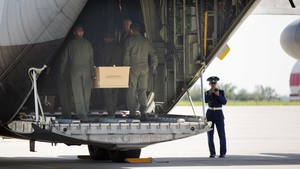 Soldiers carry a coffin on board a plane ahead of the journey to the Netherlands