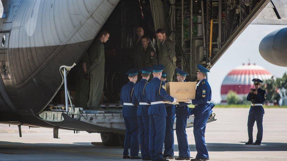 Soldiers load a coffin onto a military transport