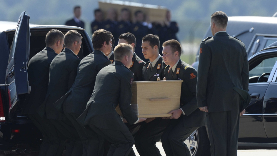 One of the coffins is placed into a hearse at the airport