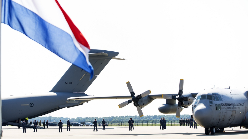 Dutch national flag flies at half-mast as the Dutch Air Force C-130 Hercules plane (R) and an Australian Royal Australian Air Force C17 transport plane arrive at Eindhoven