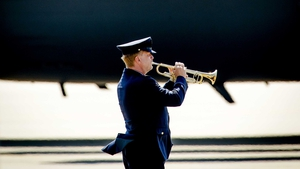 A lone trumpeter plays the Last Post as the coffins are taken from the planes