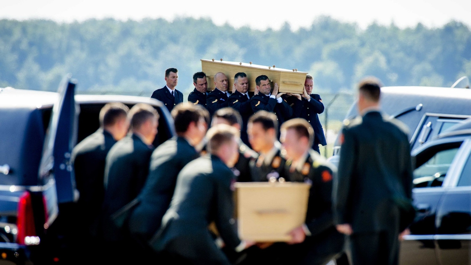 Soldiers and marines carried the coffins to 40 waiting hearses lined up on the runway