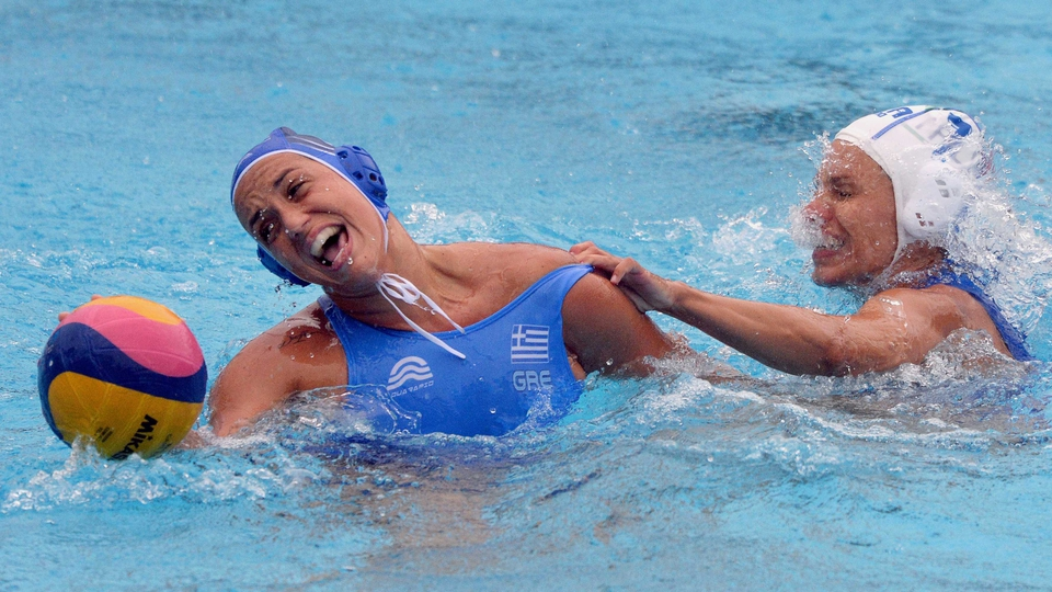 Italy's captain Tania di Mario (white) fights for the ball with Greece's Eleftheria Plevritou (blue) during the women's Water Polo European Championships match on Tuesday