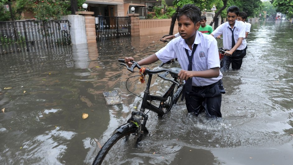 Indian school boys wade along a flooded street following heavy rains in Ahmedabad