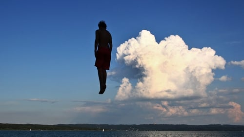 A man jumps from a tower at a public bathing beach into Lake Ammersee, in Utting, Germany