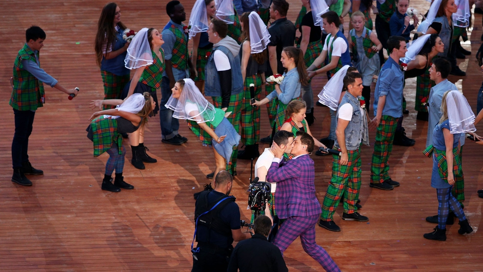 John Barrowman plants a kiss on a fellow performer during the opening ceremony for the Glasgow 2014 Commonwealth Games