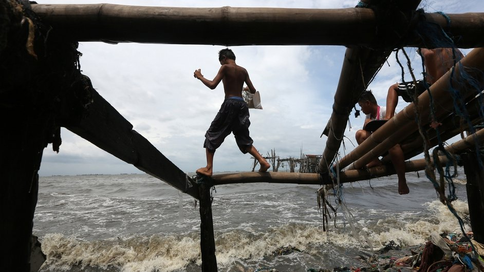 A Filipino teen stands on a bamboo frame to collect items that wash ashore in Navotas city