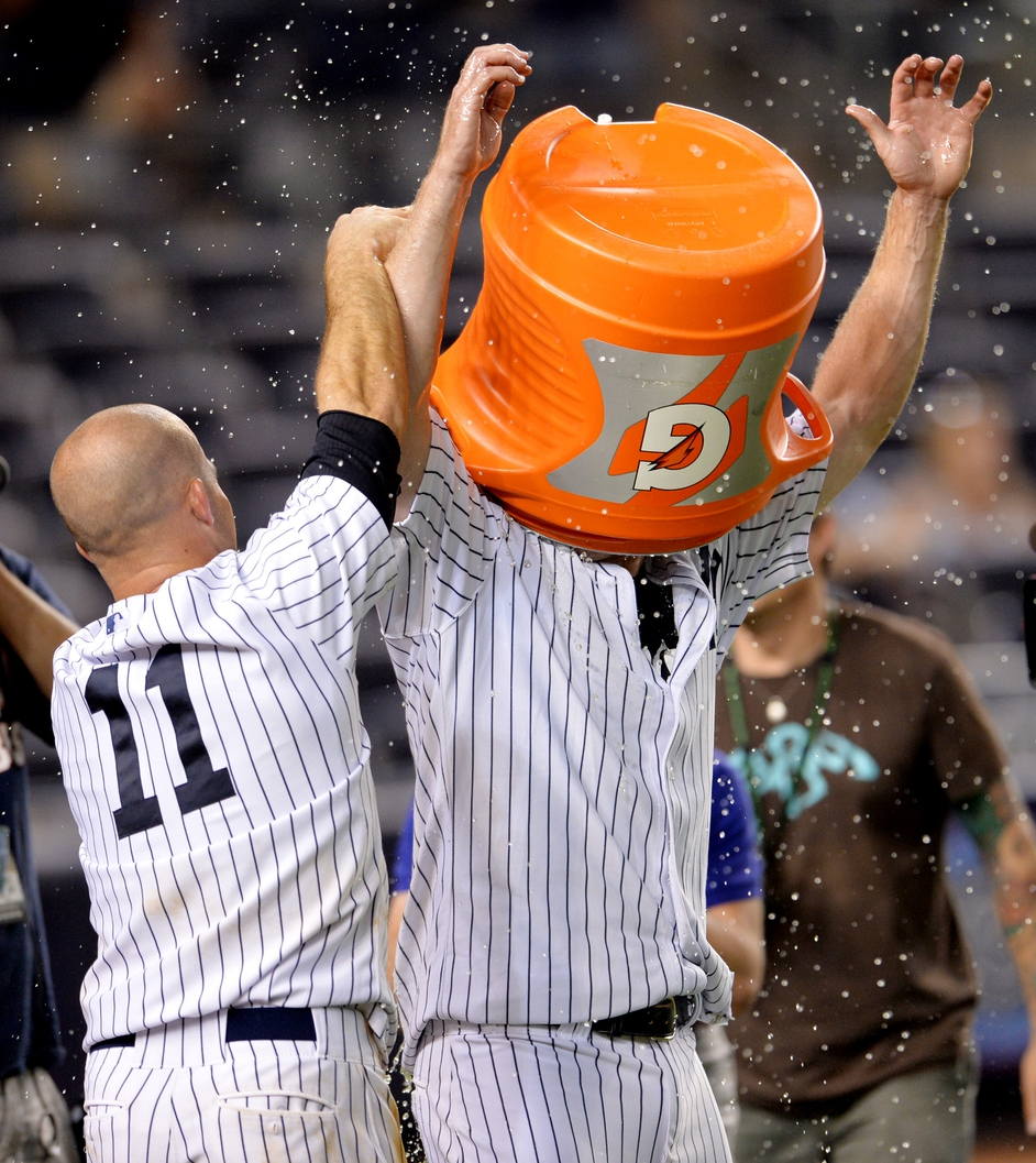 Yankees' Chase Headley (R) celebrates with teammate Brett Gardner (L) after hitting a game winning single in the game against the Texas Rangers