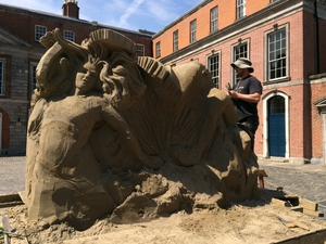 A worker works on a sand sculpture ahead of an exhibition at Dublin Castle