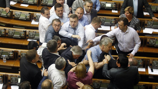 Deputies of the All-Ukrainian Union 'Svoboda' party attack the head of the Communist parliamentary faction Petro Symonenko (C) as they attempt to remove him from parliament yesterday