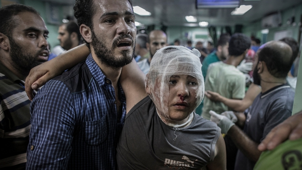 A father brings his son for treatment following the attack on the school