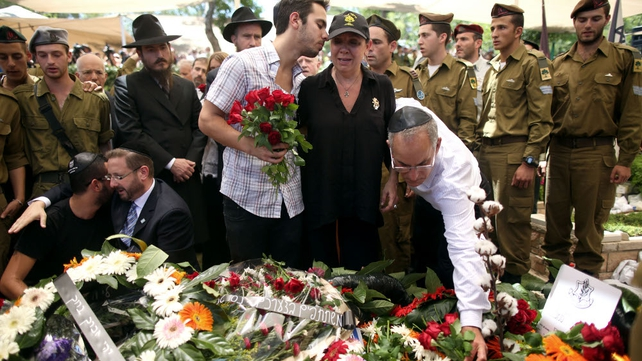 The parents of Israeli-US citizen Sergeant Max Steinberg, place flowers on his grave during his funeral in Mount Herzl cemetery