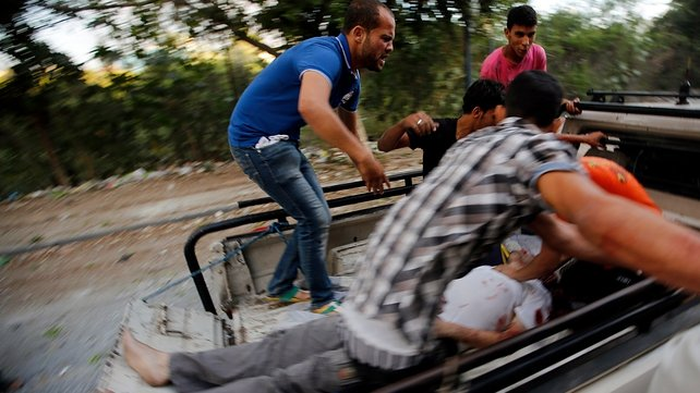 Palestinians transport a wounded man after an air strike in Al Tufah neighbourhood in eastern Gaza City
