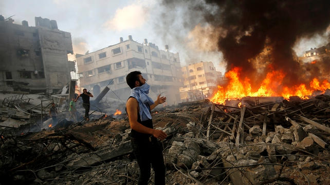 Palestinians inspect the rubble of a destroyed house after Israeli air strikes in Al Tufah neighbourhood