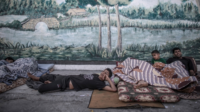Palestinian men and boys who fled with their family to a UN school sleep outside in the Jabalia district