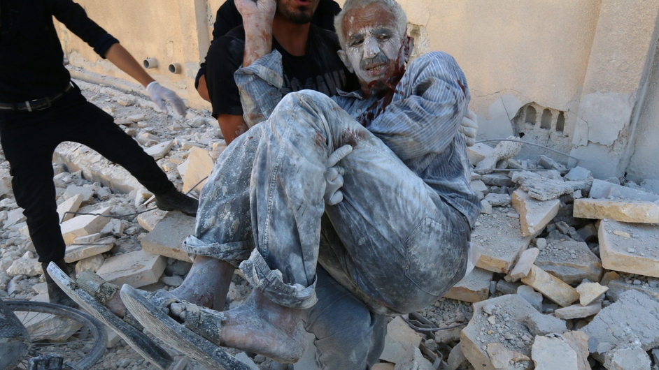 A man is rescued after a Syrian government helicopter allegedly dropped a barrel bomb on a neighbourhood in Aleppo