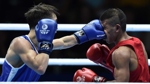 Michael Conlan (L) lands a punch to the face of Nauru's Mathew Martin during their men's bantamweight bout at the SECC