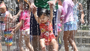 A father and his daughter enjoy bathing in the fountain at a park in Tokyo