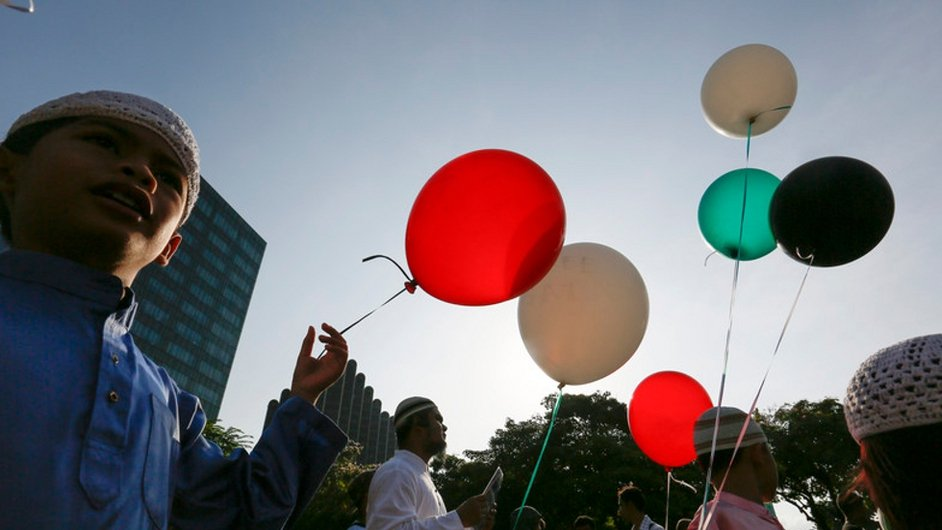 Children hold red, white, green and black balloons at Palestinian rally in Singapore