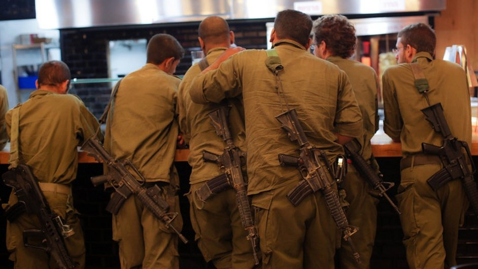 Israeli soldiers wait in line at a restaurant during the humanitarian ceasefire