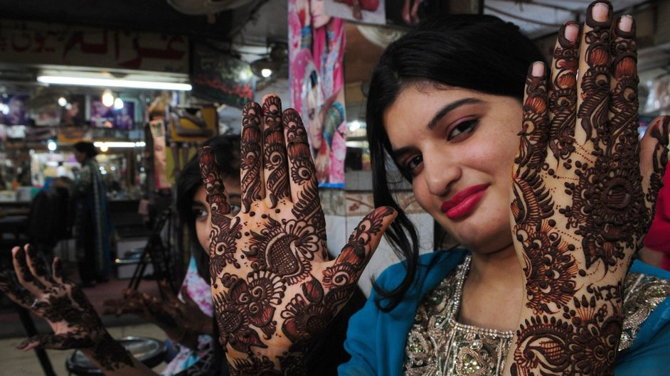 Pakistani woman displays her hands decorated with henna design ahead of the Muslim festivities of Eid al-Fitr, in Karachi