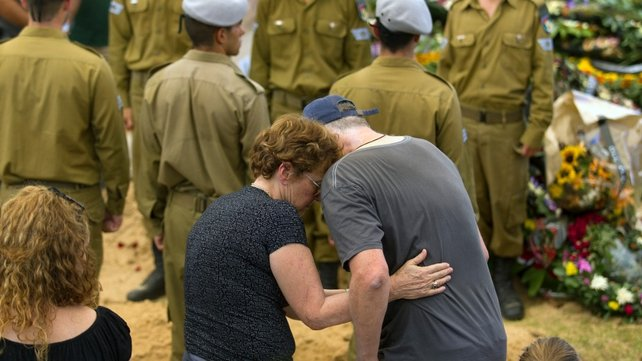 The father of Israeli soldier Staff Sgt Amit Yeori, 20, with a family member at his son's grave during his funeral