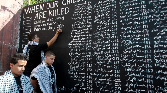 Palestinian youths list the names of the children killed in the Israeli military offensive in Gaza