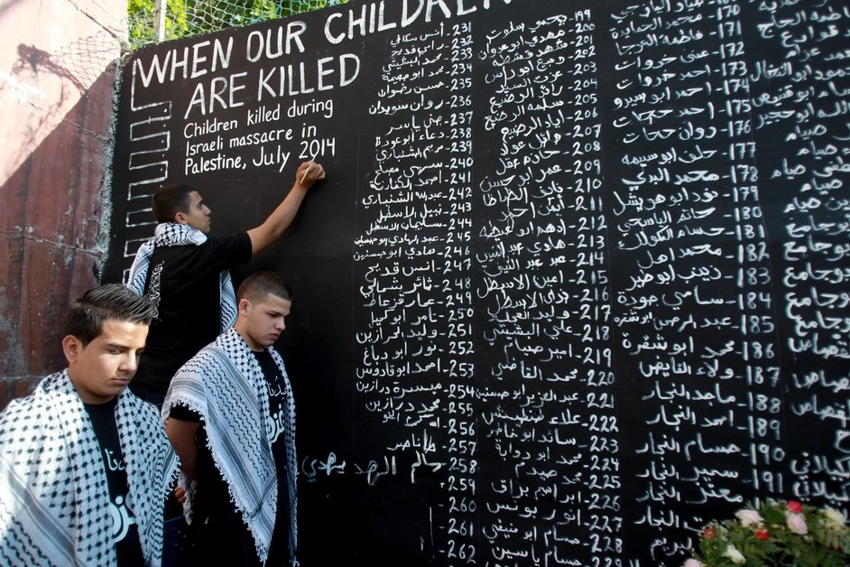 Palestinian youths list the names of the children who were killed in the ongoing conflict in Gaza