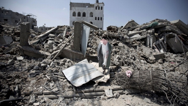 A Palestinian man inspects the rubble of destroyed buildings and houses in Gaza City