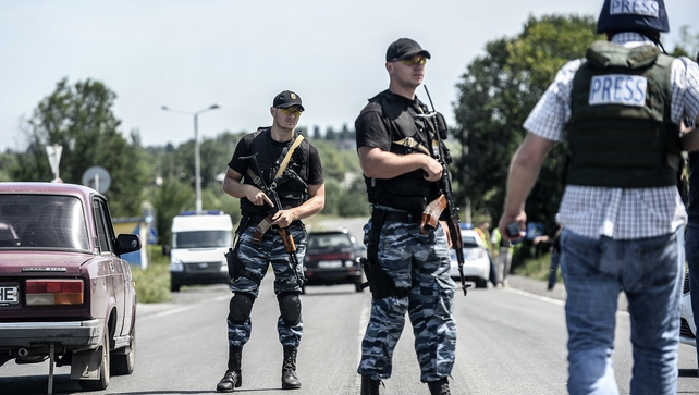 Pro-Russia militants block the road behind Dutch and Australian forensic teams on their way to the MH17 crash site