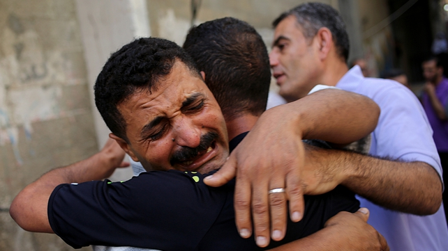 A father of two of the eight children killed in Israeli airstrikes cries outside a refugee camp