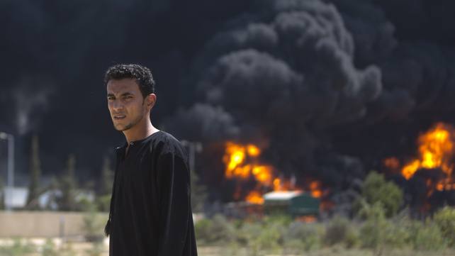 A Palestinian looks on as the only power plant supplying electricity to Gaza burns